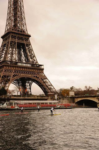 The Eiffle Tower with paddle-boarders on the adjacent river