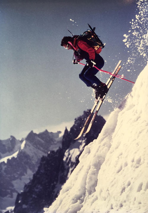 Skier leaping down a slope